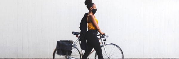 a woman wearing a face mask with her bicycle