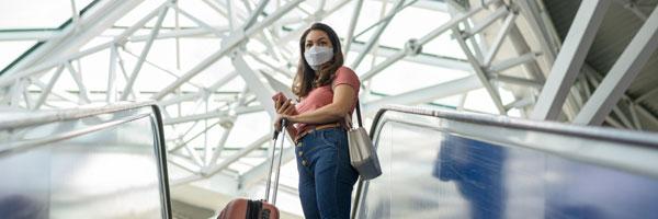 a woman wearing a mask stands on an escalator inside an airport