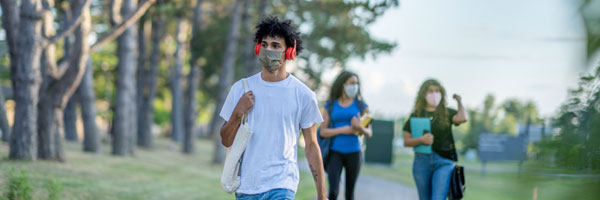 a male college student walks across campus while wearing a mask. two female students walk nearby