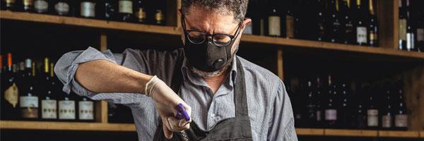 restaurant worker wearing a mask opening bottle of wine