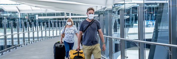 travelers are seen inside an airport wearing masks