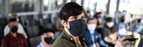 Businesswoman speaking at a business conference wearing face mask