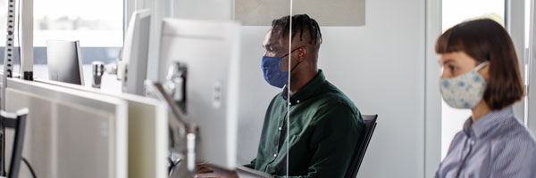 workers wearing masks sitting in an office with dividers