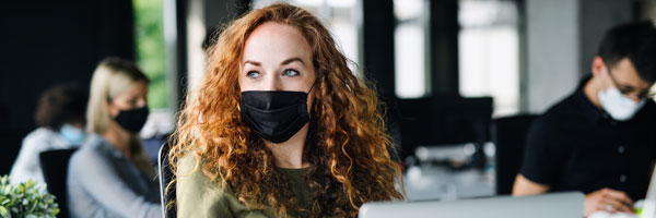 A woman wears a masks inside office