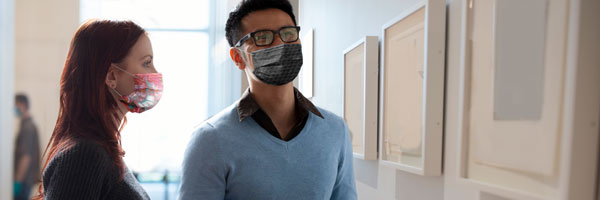 A couple wearing face coverings view framed artwork at a museum