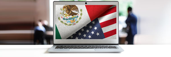 a laptop shows a Mexican flag and United States flag folded side by side
