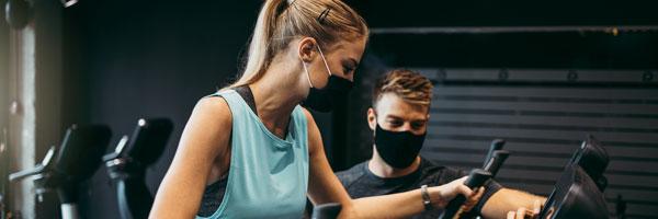 people exercising in gym wearing masks