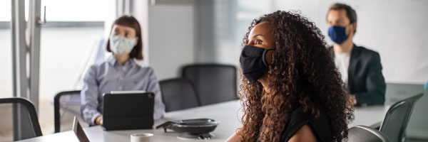 business people having meeting wearing masks and sitting socially distant