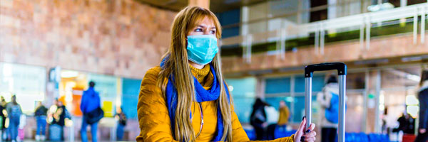 A woman in a mask sits in an airport