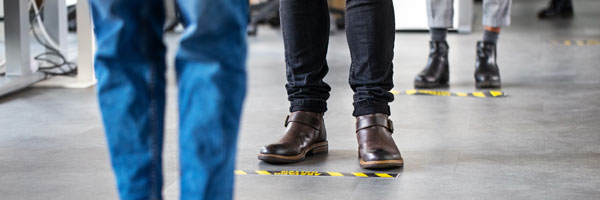 people stand in line while maintaining social disctance. photo focuses on the peoples shoes