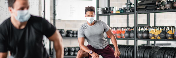 masked men exercise in a gym while maintaining social distance