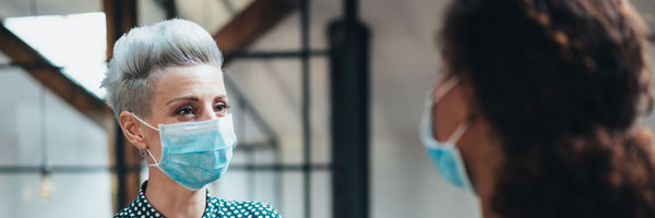female coworkers talk to each other inside an office while wearing masks