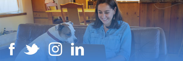 a woman sits on her couch with her dog while reading social media on her laptop