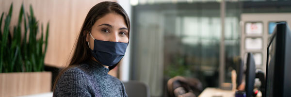 a woman sits in an office while wearing a mask