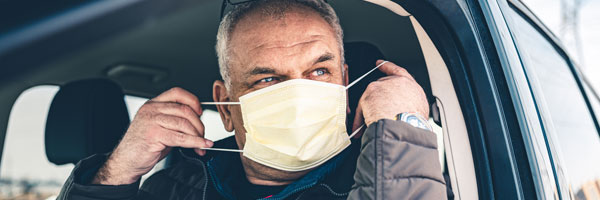 A man puts on a mask while sitting in a car