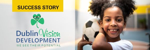 Dublin Vision Development logo and young girl carrying a soccer ball inside a gymnasium
