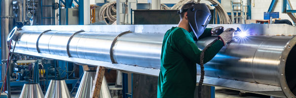 a man welds on a large pipe