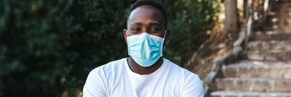 a man stands outside wearing a face mask