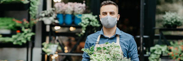 a masked employee stands inside a garden center holding a plant