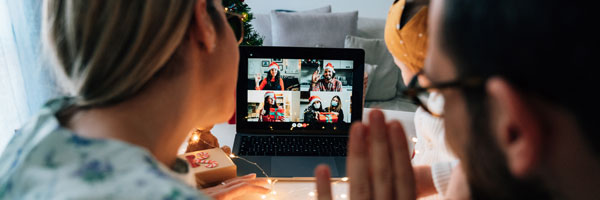 Family celebrating socially distant holidays using computer