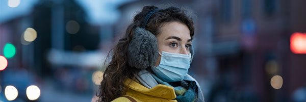 a woman stands outside wearing a mask