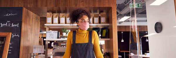 a female barista stands behind a counter at a coffee shop