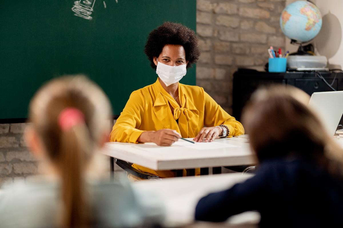 Teacher, who is wearing a mask, sits at the front of a class of students.