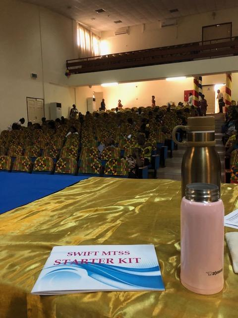 photo of an auditorium with people coming in and in the foreground a table with the speaker's water bottle and a SWIFT Starter Kit document