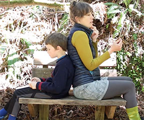 Mother and son sitting in the forest