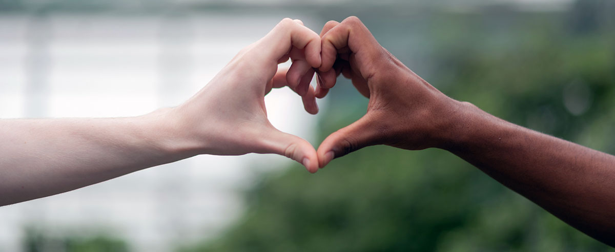 A black hand and a white hand making a heart together