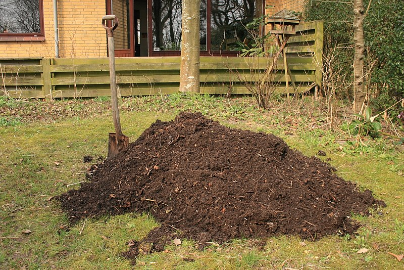 picture of fresh compost pile in garden area with shovel