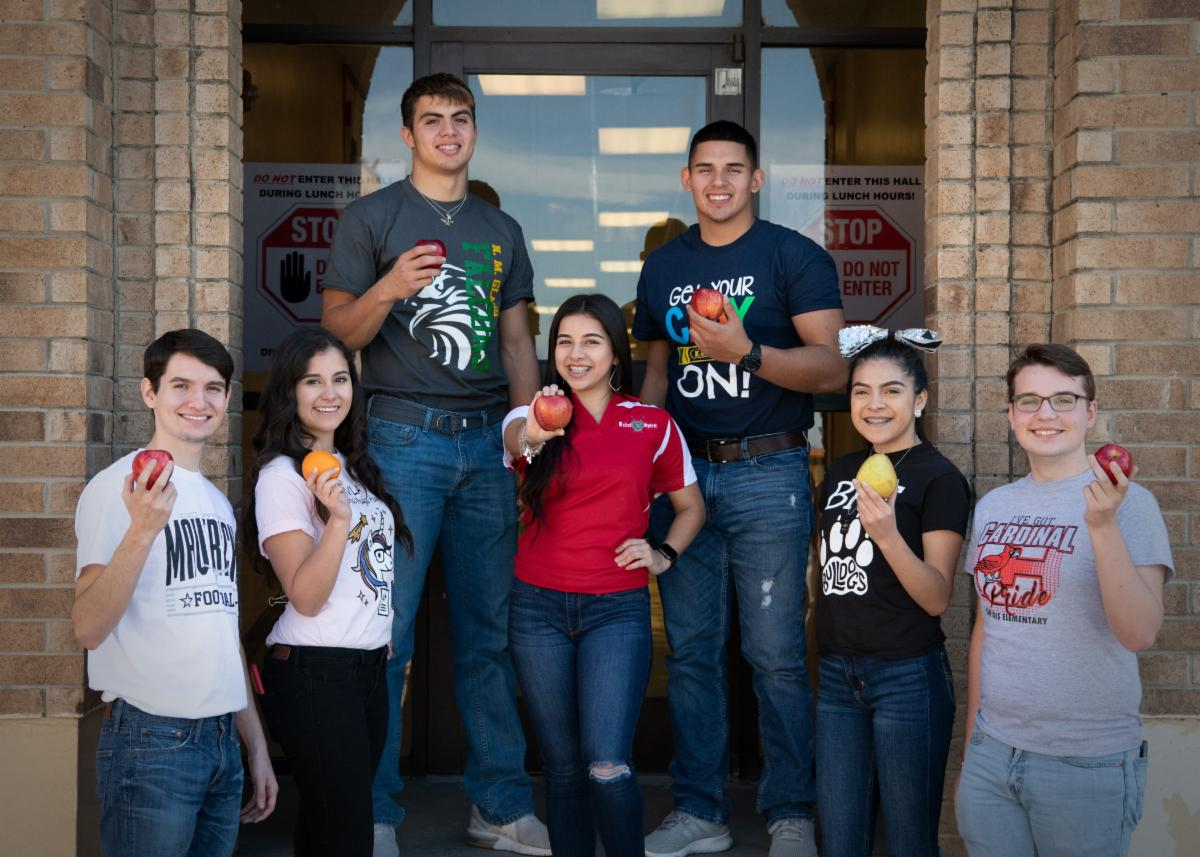 Group of teenage Texas students smiling and holding an apple in front of their school building.