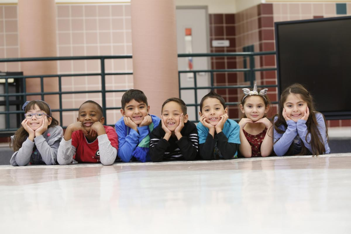 A group of seven elementary aged students is laying on the floor resting their elbows on their chins while they smile at the camera.