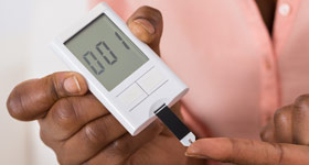 close up of hands doing diabetes blood sugar test