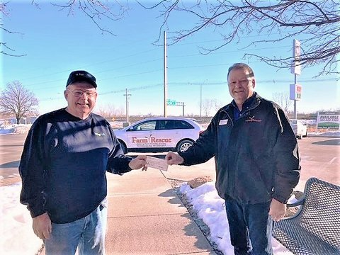 Pic of Tim Sullivan from Farm Rescue on Rt handing a $1000 check to Rod Peterson of NE AgrAbility outside on a sunny cold day.