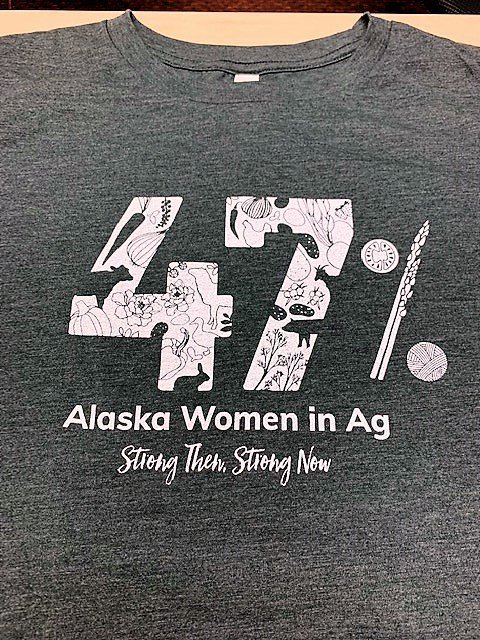 Gray T-shirt on cream background with white printing that says 47% Alaska Women in Ag Strong Then - Strong Now