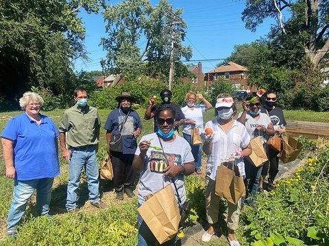 Multi-racial group carrying paper bags and displaying different vegetables in garden rows next to raised bed gardens