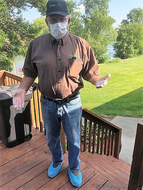 Rod wearing PPE mask - gloves - and shoe coverings - while standing on a wood deck
