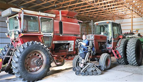 Photo of a man standing in a warehouse next to a large red tractor standing on a machine that helps assist him getting onto the tractor