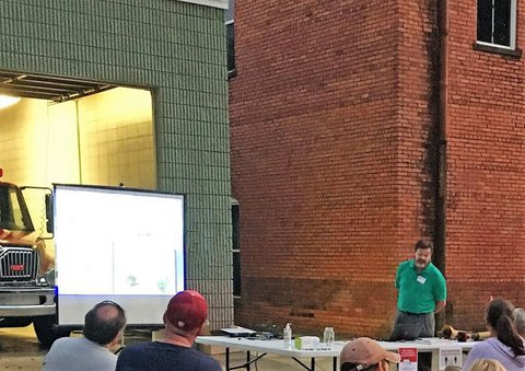 GA AgrAbility staff presenting a PowerPoint on a screen in Pike County outside of large gray building on left and large red-brick building on right
