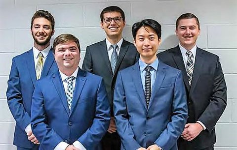 MSU chain hoist team (5 men in suits) standing in front of a cement brick wall