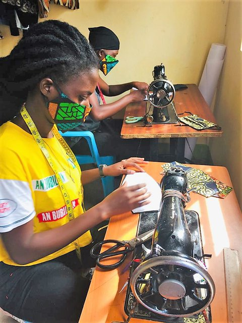 Two african women in a room wearing facemasks like they are making on tredal-style sewing machines