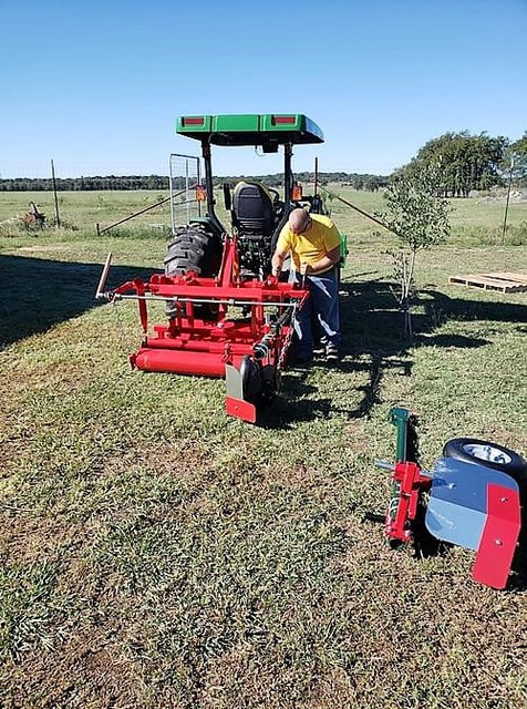 Damon Kleaton in a yellow shirt in a field working on his tractor with the red plastic mulch and irrigation layer attached