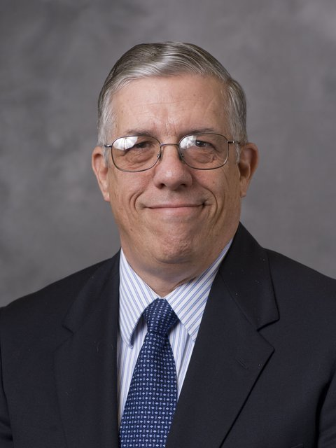 Portrait of Steve Swain in dark suit coat with a blue and white striped shirt and dark blue and white  tie.