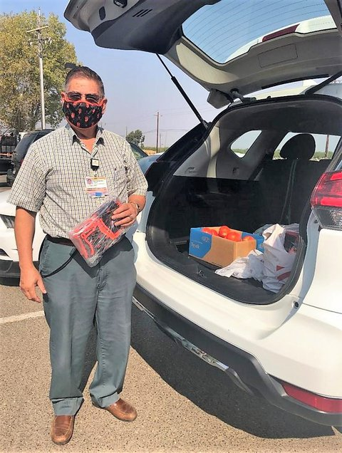 Man with face-mask on and holding a sack of face-masks standing behind a white car with its hatchback open