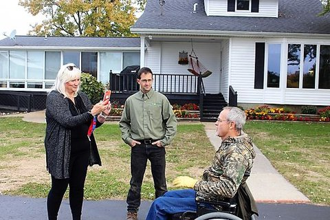 Two people standing in front of a white house with a black porch and hammock on the porch recording a video of older gentleman in a wheelchair.