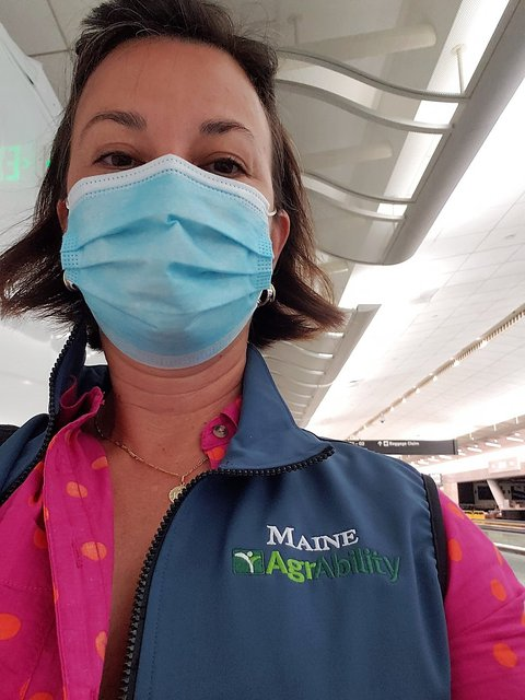 Picture of Anne with blue face mask on and blue Maine AgrAbility vest over a pink blouse