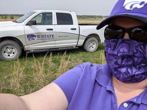 Person with a purple cloth face mask on in front of a white Kansas State pickup truck