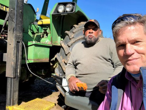 Frank Beard (back left) on John Deere tractor lift seat holding lift control in his left hand with another person on right side of picture take selfie with Frank and blue skies overhead