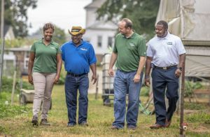 Three USDA workers and a farmer walk in farm yard with high tunnel greenhouse in background